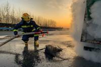2月18日,湖北襄阳,一辆满载防疫物资的货车在驶至汉十高速钟岗服务区时,车辆轮胎起火,消防员仇涛正在用水枪进行灭火。刘永正 摄