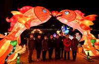 3月20日晚,天津市对口支援湖北恩施医疗队的队员们在宣恩县城贡水河畔的彩灯前合影留念。