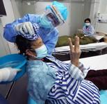 护士长冯晶在给78岁患者张大妈洗头(3月20日摄)。张大妈伸出三个指头对同房病友说,这是护士长第三次给她洗头了。