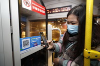 3月25日,在武昌火车站综合体站始发的首趟518路公交车上,乘客用手机支付宝APP扫码实名登记,显示健康绿码后方可乘车。