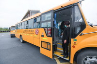 3月26日,在人大附中杭州学校举行的防疫演练中,工作人员对校车进行消毒。