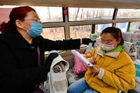 山西省静乐县第一中学校车上的工作人员在给李彦昀(右)测量体温(3月25日摄)。