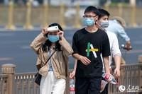 5月1日,路上的行人遮挡烈日。(人民网记者 翁奇羽 摄)