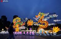 2020年5月4日,江苏常州,游客从5A旅游景区中华恐龙园龙凤呈祥造型彩灯边走过。