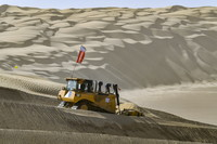 在新疆尉犁至且末沙漠公路施工现场,工人驾驶大型推土机推平沙山(5月16日摄)。