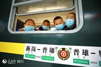 在普雄站乘坐5633次列车的彝族儿童旅客。(李锴 摄)