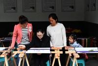 5月14日,李绍玉(左二)在位于重庆彭水县高谷镇共和村的非遗扶贫工坊演示手工刺绣。新华社记者 王全超 摄