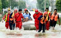 7月20日,救援人员用橡皮艇将被困群众送往安全地带。
