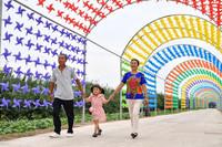 7月19日,东风镇村民在开鲁县东风镇东七家子村万亩果品经济林示范区的风车长廊里游玩。 新华社记者 贝赫 摄