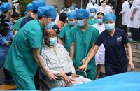 7月21日,武汉大学人民医院医护人员护送崔先生出院。