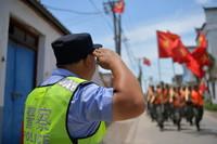 7月22日,梅玉胜向经过他们驻点的参加防汛抗洪的战士敬礼。