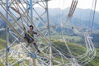 2020年7月23日,在河北省保定市涞源县,安徽送变电工程有限公司施工人员在80多米高的1000千伏特高压输电导线上施工。郑贤列/人民图片
