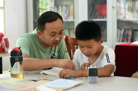 """7月22日,在枞阳县横埠镇方正小学安置点""""爱心教室""""里,方正小学老师操磊(左)指导小朋友写暑假作业。"""