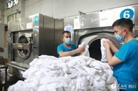 7月22日,成都客运段整备一车间卧具洗涤工将清洗完的普速列车卧具取出。(苏志刚 摄)