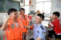 """""""我要给警察叔叔敬礼!""""7月22日,安徽和县一群众安置点,王嘉豪小朋友(左一)对上安全课的警察说。"""