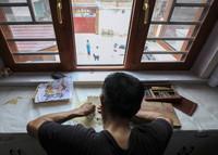 8月1日,皮影艺人蔡善存在家中雕刻制作皮影。