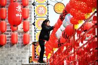 12月25日,江西省樟树市三皇宫历史文化街区的工作人员悬挂红灯笼。