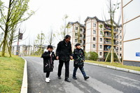 12月23日,在大方县奢香古镇易地扶贫搬迁安置点,李昌德(中)牵着李思宇(右)、李青怡放学归来。