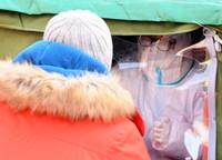在北京市顺义区双丰街道香悦西区采样点,医护人员为被检测人员采集核酸样本(1月3日摄)。新华社记者 任超 摄