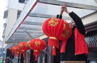 1月5日,东林镇星华村的党员志愿者在新农村新居给村民挂红灯笼。