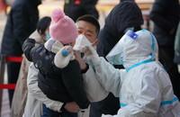 1月6日,在石家庄市桥西区恒大城内的核酸检测点,一名小朋友在家长的陪同下接受核酸采样。新华社记者 牟宇 摄