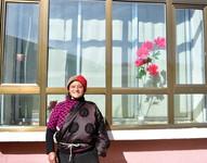 1月11日,隆亚村牧民索吉在搬迁点的新家前留影。