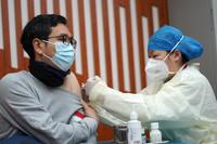 1月14日,在北京市东城区崇外街道临时接种点,来自北京市普仁医院的工作人员在为接种人员接种新冠疫苗。