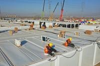 1月17日,工人在石家庄黄庄公寓隔离场所项目工地集成房屋屋顶安装空调设备(无人机照片)。 新华社记者 杨世尧 摄