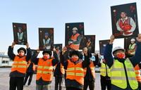 """1月18日,中建一局北京城市副中心工地的建设者代表们展示自己的""""微笑""""照片。"""