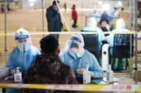 1月20日,在北京市大兴区庞各庄镇一处核酸检测点,医护人员为参加核酸检测的人员进行采样。新华社记者 鞠焕宗 摄