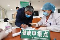 1月21日,在南京市玄武区玄武门社区卫生服务中心,来自江苏省肿瘤医院的一线医务人员(左)在疫苗接种前进行健康申报。