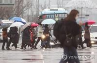 21日,韩国首尔迎来降雨,行人匆匆经过光化门前的十字路口。