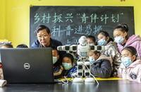 """1月21日,在贵州省毕节市黔西县锦绣街道""""新市民·追梦桥""""服务中心,科普宣传员给易地扶贫搬迁安置点儿童讲解机器人的操作原理。"""