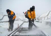 铁厂沟维修工队的工人王天兵(左)和工友在清除一处铁轨道岔上的积雪(1月20日摄)。