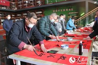 书法家协会的会员为居民书写着一幅幅特别的理论春联。  方晗摄