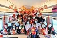 2月9日,C6409次列车上列车工作人员与旅客合影,并送出新春祝福。包亮摄