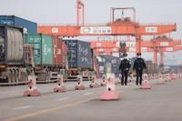 民警雷激(右)和同事对进出中心站集装箱装载区货车进行巡查。胡勇摄
