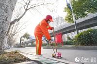 图为环卫工人正在打扫路面卫生。喻华轩摄