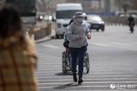 3月28日,路上行人头戴面纱和口罩,做好全面防护。人民网记者 翁奇羽摄