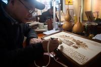 """4月1日,在合肥市明光路街道非遗工作室,安徽省葫芦烙画省级传承人郑小良在制作以""""南湖红船""""为主题的烙画。"""