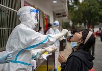 4月6日,在瑞丽市友谊社区一核酸检测点,医务人员进行核酸采样工作。