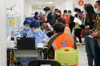 4月6日,在上海市奉贤区的新冠疫苗临时集中接种点,医务人员为工人接种新冠疫苗。