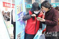 图为志愿者引导求职者扫码关注招聘信息。刘书阁摄