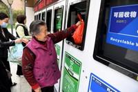 4月12日,在淝南社区垃圾分类投放站,居民使用智能垃圾分类回收柜投放垃圾。