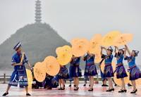 4月14日,在广西罗城仫佬族自治县成龙湖广场,仫佬族青年在表演节目。