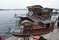 4月13日,韩鸣华拿着自己制作的红船模型站在嘉兴南湖湖心岛的红船边。