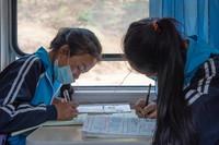 学生们在5634次列车上写作业(4月15日摄)。新华社记者 胥冰洁 摄
