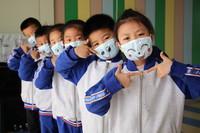 """5月7日,山东省滨州市高新区实验幼儿园的小朋友们在迎接""""世界微笑日""""活动上展示制作的""""笑脸口罩""""作品。新华社发(初宝瑞 摄)"""