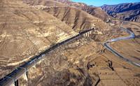 重载列车行驶在桑干河旁的大秦铁路上(2018年12月6日摄,无人机照片)。新华社记者 曹阳 摄