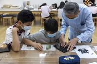 """5月11日,上海市非物质文化遗产""""漆器制作技艺""""传承人俞升涛(右一)指导学生学习刻漆技艺。"""